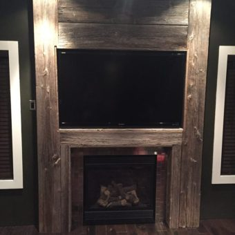 Floor to ceiling grey barnwood fireplace mantle with stainless steel tiles