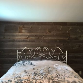 Grey barnwood bedroom feature wall with bed
